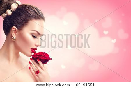 Beauty Valentine's Day Woman with red rose. Fashion Model Girl face profile Portrait with Red Rose in her hand. Red Lips and Nails. Pink blurred background. Beautiful Luxury Makeup and Manicure, hair.