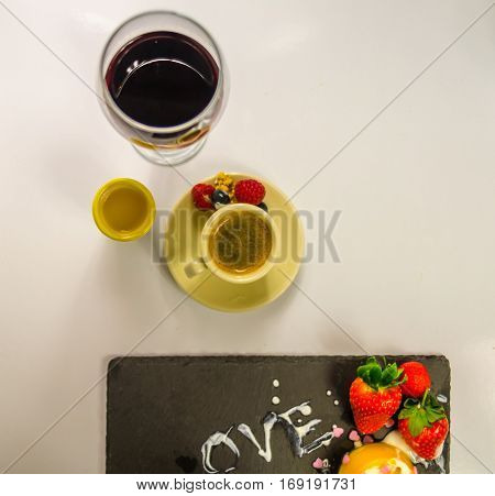 Black coffee in a cup of cream with juicy strawberry rasberry sweet set glass wine and orange juice