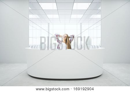 Attractive young woman relaxing at reception desk in concrete interior with city view. Mock up 3D Rendering