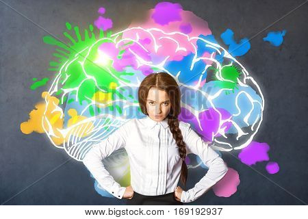 Pretty european businesswoman on dark grey background with bright colorful brain sketch. Brainstorming concept