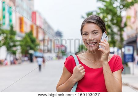 Chinese woman talking on the phone while walking on Wangfujing shopping street, Beijing city. Smart casual businesswoman using mobile app outside. Happy asian girl calling during China summer travel.