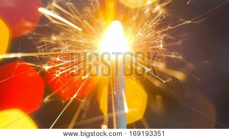 Firework sparkler burning. Elegant abstract garlands bokeh background. Extreme macro shot. Christmas and New Year concept