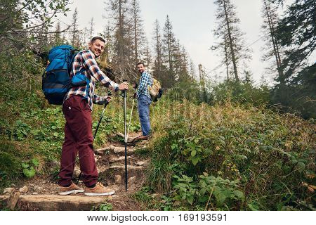 Portrait of two smiling young men wearing backpacks and carrying trekking poles walking up a trail together in a forest