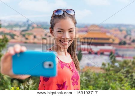 China travel. Young Asian woman tourist taking selfie pictures with mobile phone with background landscape view of the Forbidden City in Beijing. Asia summer destination.
