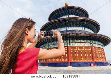 Asia travel chinese woman tourist taking picture with smartphone of the Temple of Heaven, a popular touristic attraction which is an imperial building in Beijing city. Famous China landmark.