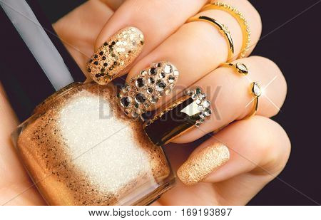 Golden Nail art manicure. Holiday style bright Manicure with gems and sparkles. Bottle of Nail Polish. Fashion rings with diamonds, Trendy Accessories. Beauty hands. Stylish Nails, Nailpolish.