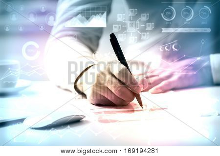 Close up of man doing paperwork at workplace with creative business charts and diagrams. Toned image. Accounting concept