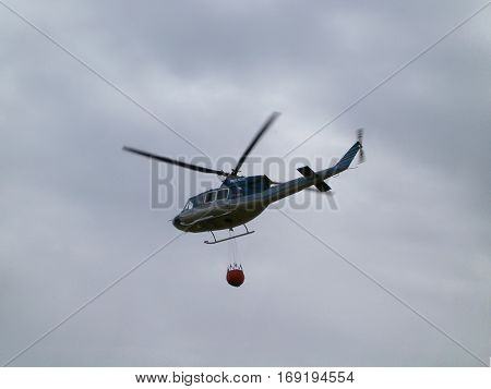 Photo of a police helicopter with a helicopter bucket