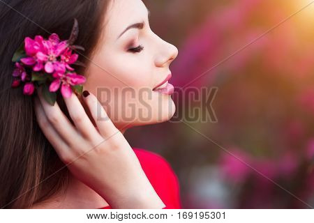 Happy beautiful young woman in spring blossom park at sunset. Attractive female in red dress enjoy spring fresh pink flowers.