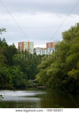 Photo of several apartment buildings in front of a river surrounded by greenery