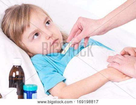 Mother holding thermometer and sick little girl in bed. Portrait of illnes kid with fever, resting at home.