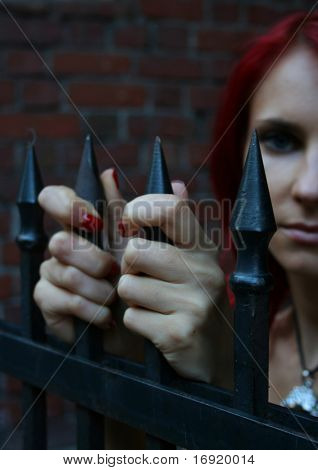 girl under the metal fencing