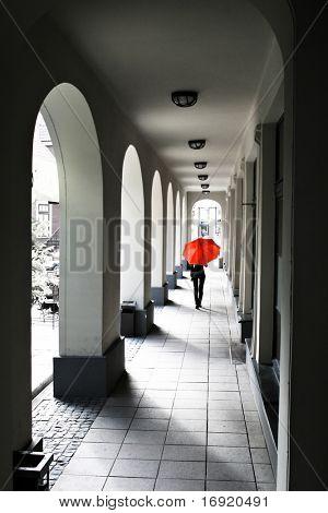 walking girl under red umbrella
