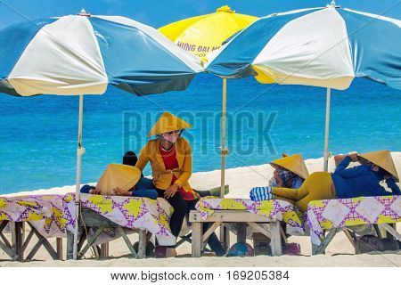 PHU QUOC, VIETNAM - APRIL 21, 2014: Beach masseuses resting  waiting of tourists in the shade of umbrellas at Long beach on Phu Quoc island, Vietnam.