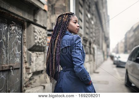 Black haired girl wandering around on the street in blue jacket