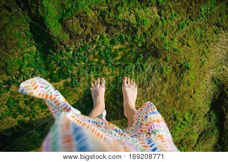 High angle view of woman standing on the beach during summer vacation. Girl in waving sundress looking at her feet