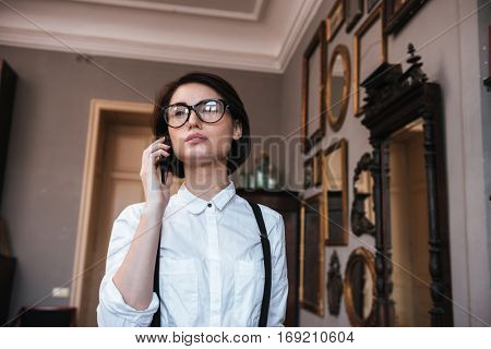 View from below of Authoress in glasses and white shirt talking on phone