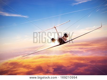 Private jet plane flying above clouds in beautiful sunset. Shot from backside. High resolution image
