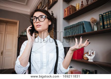 Pretty Authoress in glasses and white shirt talking on phone and looking up not understand gesture