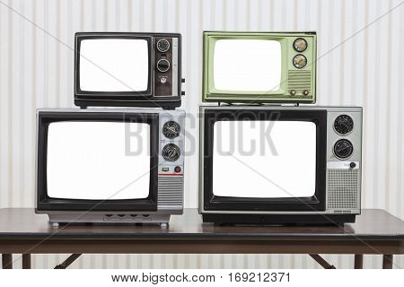 Four vintage televisions on table with cut out screens.