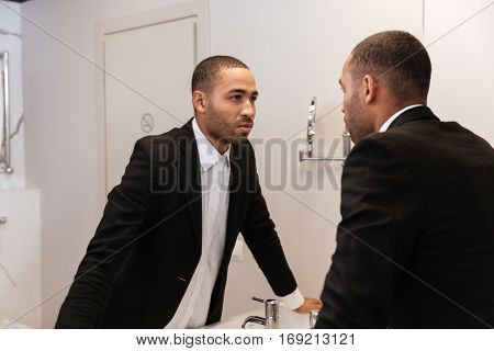 Back view of African man in suit looking at mirror in bathroom in hotel room