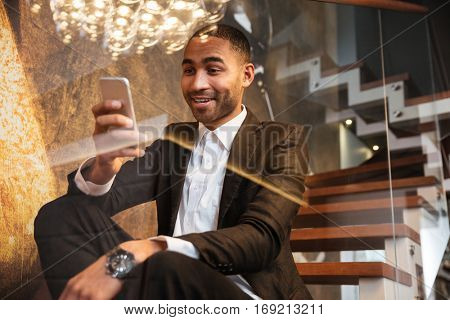 View from below of surprised african man in suit using phone and sitting on stairs