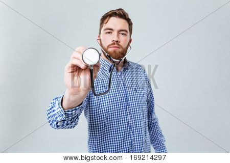 Serious bearded young man in plaid shirt using stethoscope