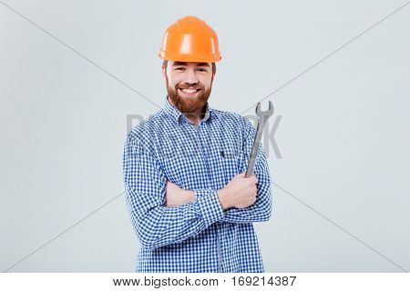 Happy bearded young man in orange helmet standing and holding wrench