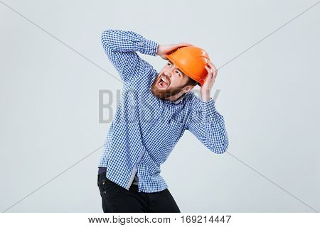 Shocked bearded young man in helmet covered his head by hands and screaming