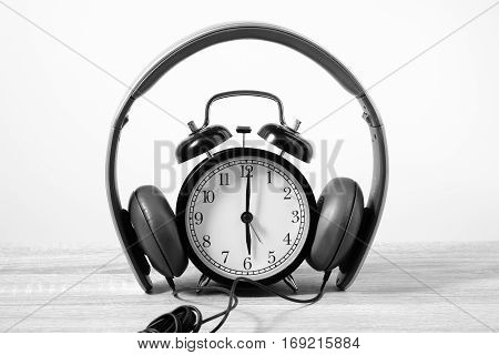 Front View Alarm Clock Put On Headphones Over Wooden Table. Timeless Music Concept.