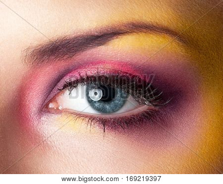 Beauty makeup yellow magenta eyes retouched skin with blue eye poster