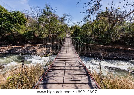 Rope walkway through the river in a rain forest.