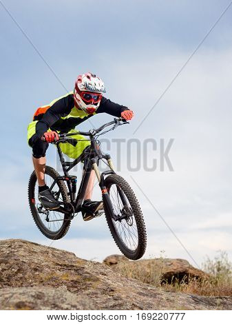 Professional Cyclist Riding the Bike Down Rocky Hill. Extreme Sport Concept.