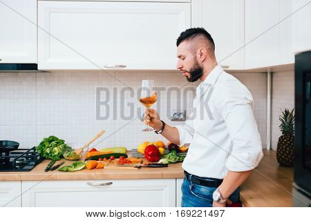 Details Of Perfect Dinner. Confident Male Sommelier Looking At Wine Glass Standing In Modern Kitchen