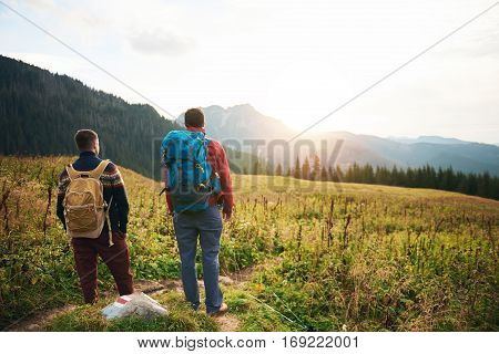 Rearview of two young men in hiking gear standing in a field watching the sunrise while out treakking in the wilderness