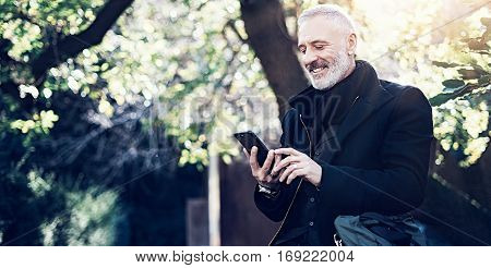 Portrait of smiling middle age businessman using modern smartphone while spending time in city park at sunny day.Horizontal, blurred background