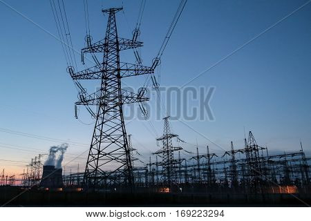 Sun setting over an electrical substation blue silhouettes