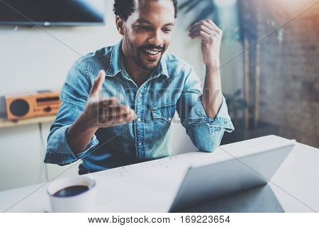 Smiling young African man making video conversation via digital tablet with business partners while sitting in sunny meeting room.Concept of happy coworking people.Blurred background, flare
