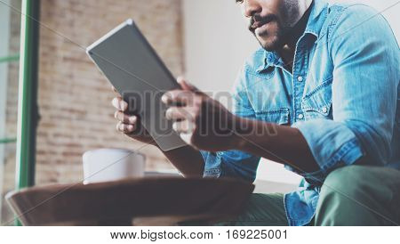 Pensive African man using tablet for video conversation while relaxing on sofa in modern office.Concept of young business people working at home.Blurred background.Selective focus, crop.
