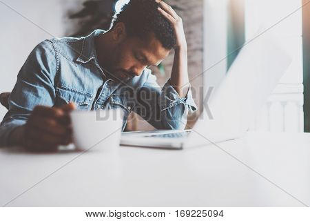 Tired young African man using laptop while sitting at the table on a sunny morning.Concept of people working hard home.Blurred background, flare effect