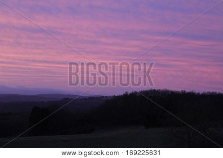 Sunrise in Häselingen on February 4, 2017 on a Saturday morning, in the foreground a pasture,    In the background the impressive sky the colors in pink - purple - blue And in black forests of Krählingen and surroundings of the municipality Berg