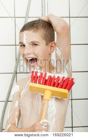 Young Boy With Broom Brush In The Shower