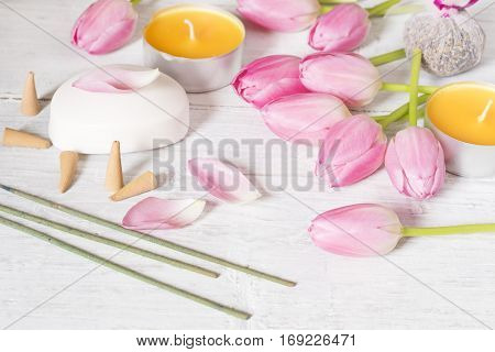 Candlestulips soap and incense sticks on white background