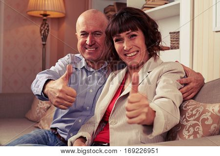 A mid shot of two marrieds demonstrating their thumbs-up, having fun, grinning broadly. Man embracing his lady warmly and with love