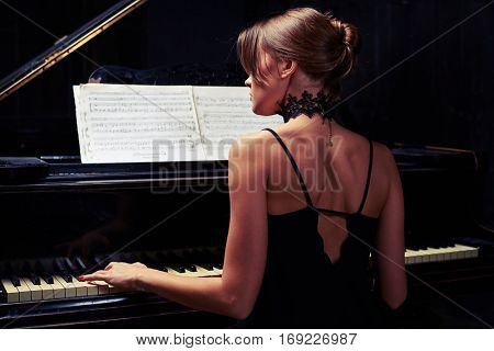 Back view of young woman sitting down to the piano in black back naked dress in sombre studio. Glamor beautiful brunette in a black sexy dress with open back