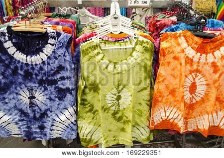 Row of colorful Apparel on Shoulders Hangers of Gondola of Retail Shop with other Items on Background