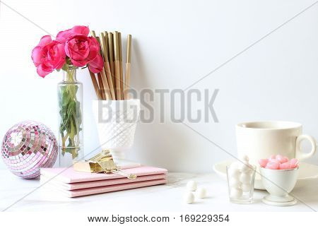Styled wall and desk scene with elegant white and pink décor.