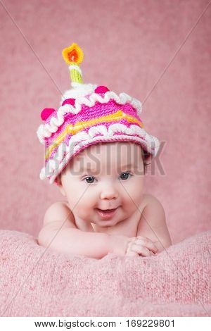 Newborn baby in warm knitted hat the form of cake with a candle.