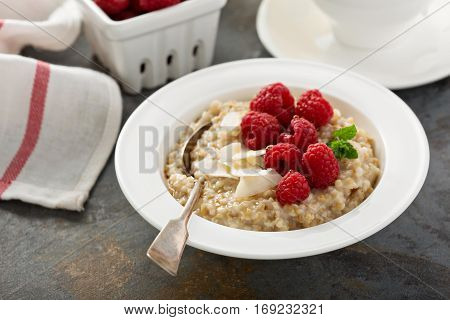 Steel cut oatmeal porridge with raspberry and coconut flakes for breakfast