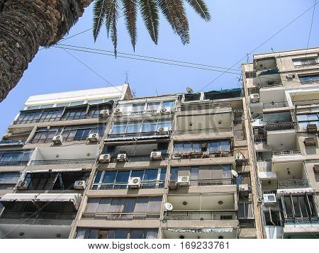 Old apartment building in Cairo Egypt with balconies air conditioner units and satellite dishes